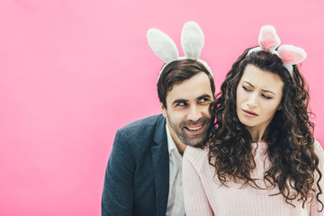 Young lovers couple on the pink background. With a bunny ears on the head. Putting his head on his wife's shoulder, a man looks in love with a woman while he is not satisfied. Easter.