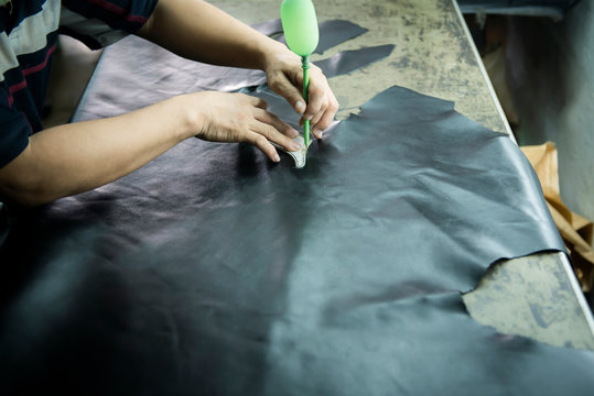 Shoe maker drawing on a genuine leather. To prepare for shoe making handmade on a lap.
