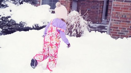 Wall Mural - Slow motion. Little girl in pink hat playing in snow.