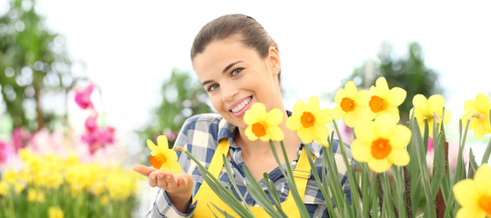 smiling woman in garden of flowers touch daffodils, spring flowering concept