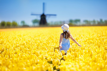Kids in tulip flower field. Windmill in Holland