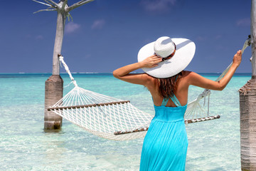 Attractive woman in a blue summer dress stands in tropical, turquoise waters in front of a hammock and enjoys her vacation