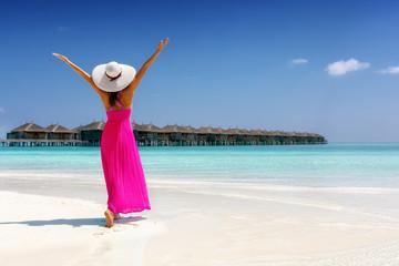 Glückliche Frau im pinken Sommerkleid genießt den Ausblick auf einen tropischen Strand mit türkisem Meer auf den Malediven