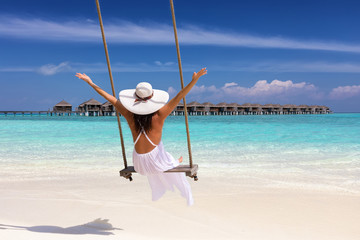 Tropical vacation concept: happy female traveller in a white dress on a swing enjoys her summer holiday