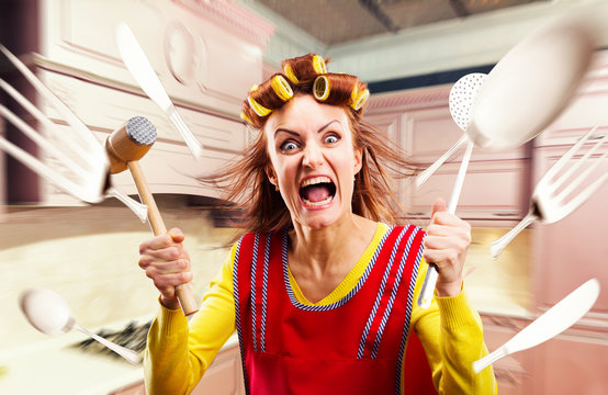 Crazy housewife in apron cooking, cookware flying