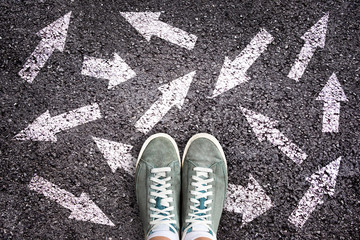 Sneaker shoes and arrows pointing in different directions on asphalt ground, choice concept