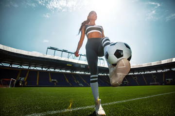 Athletic sporty woman in sportswear with soccer ball on stadium.