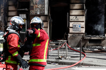 """Firefighters stand at the entrance of a burnt Tarneaud Bank near the Champs-Elysees avenue, during clashes with riot police forces during a demonstration by the """"yellow vests"""" movement in Paris"""