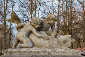 Zwei Kinder berühren einem Fisch aus Stein