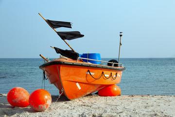 Oranges Fischerboot mit schwarzen Fahnen am Strand