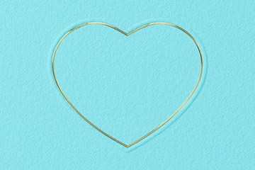 Heart-shaped frame made of  glossy gold on turquoise textured background