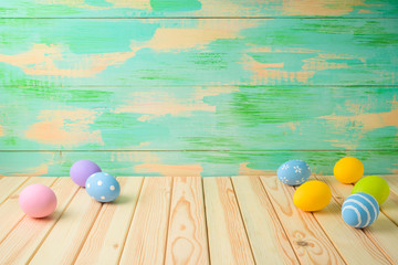 Empty wooden table with Easter eggs over colorful background.