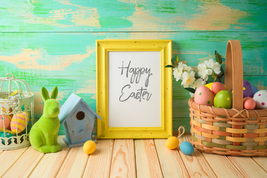 Photo frame or artwork display mock up on wooden table with easter decorations.