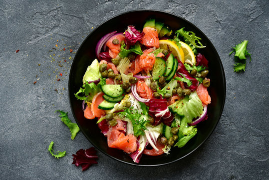 Vegetable salad with salted salmon in a black bowl.Top view with copy space.