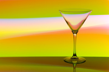 A cocktail / martini glass with colorful streaks of light painting behind