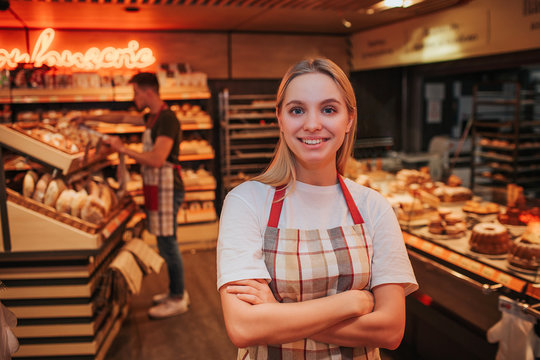 Happy young woman stand in grocery store. She pose nad look on camera. Happy worker smiling. Young man work behind. He put bread on shelf.