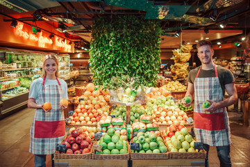 Young man and woman stand at fruit boxes in grocery store. They hold citrus in hands and smile. Workers look straight and pose on camera. Wall mural