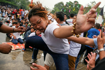 A devotee in trance mimics a beast during a religious tattoo festival at Wat Bang Phra monastery, where devotees believe that their tattoos have mystical powers, in Nakhon Pathom province