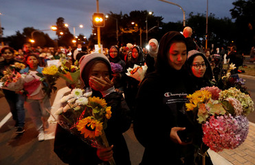 People reacts as they move the flowers after police removed a police line, outside Masjid Al Noor in Christchurch