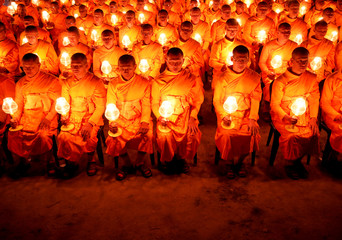 """Monks with lit candles attend an event to spread the message of """"world peace through inner peace"""" in Kathmandu"""