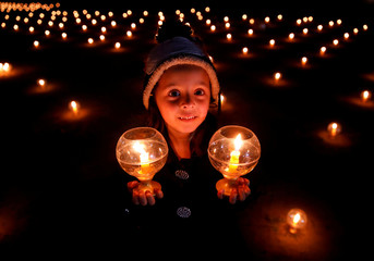 """A girl with lit candles attends an event to spread the message of """"world peace through inner peace"""" in Kathmandu"""