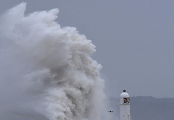 People watch as large waves crash against the seawall during strong winds at Porthcawl, Britain