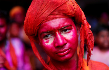 A Hindu devotee takes part in the religious festival of Holi inside a temple in Nandgaon