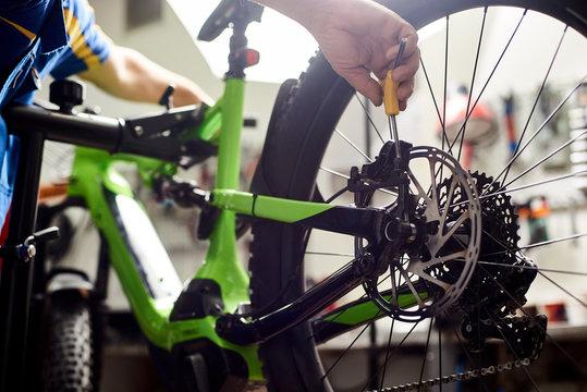 Cropped shot of male mechanic working in bicycle repair shop, serviceman repairing modern bike brakes using special tool, wearing protective workwear