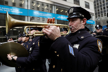 A member of the New York City Police Department (NYPD) marching band plays the trumpet as he marches in the 258th St Patrick's Day Parade in New York