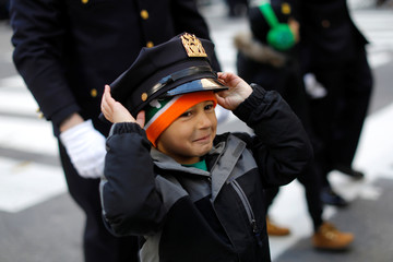A young boy trys on a Police officer's hat as he marches in the 258th St Patrick's Day Parade on 5th Avenue in New York