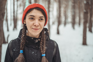 Girl Eastern looks walking in the forest in the winter. Cheerful and beautiful woman posing in the Park. Concept: a walk in the fresh air, the guarantee of health and good mood