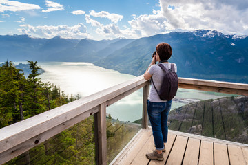 Woman Hiker Taking Photos from a Viewing Deck on the Top of a Mountain. Impressive Panorama. Squamish, BC, Canada.