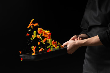 Chef prepares vegetables. freezing in motion. on black background. cooking background