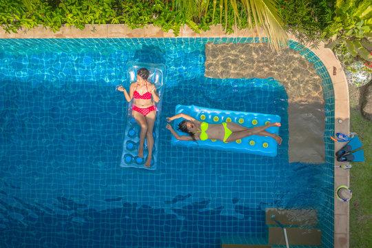 aerial top view above swimming pool. woman in yellow bikini and woman in red bikini sleep on swimming pool inflatable .mattress float in villa pool