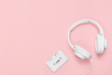 White cassette tape and headphones on a pink background. Party 90s concept.