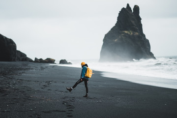 Young hipster girl walks black beach Vík in Iceland, yellow backpack and hat