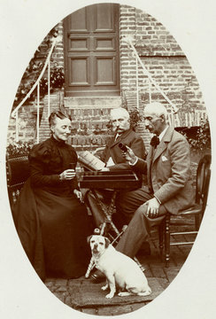 Three People with a Dog in a Garden