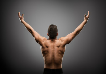 Athletic Man Raised Open Arms, Muscular Athlete Body Back Rear View over gray studio Background