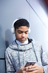 Afro american boy teenager in headphones listening to music on mobile phone. Cute black man uses smartphone outside.
