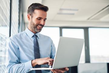 Handsome businessman in modern office working on laptop