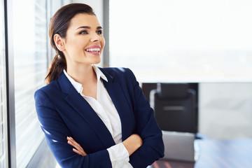 Portrait of happy businesswoman standing in modern office