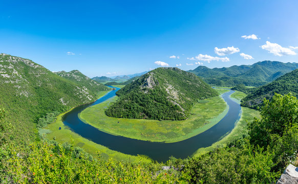 The picturesque meandering river flows among green mountains.