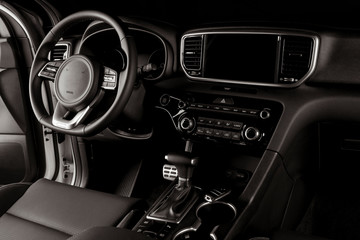 Modern car interior, automatic gearbox, steering wheel, and dashboard
