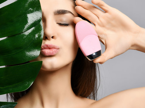 Pretty woman with closed eyes holds pink face exfoliator brush cleansing device for skin and large green leaf sends a kiss