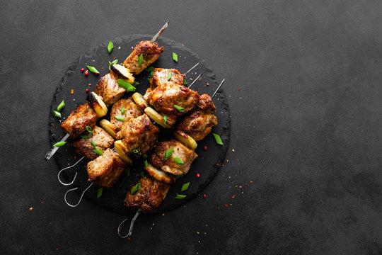 Grilled meat skewers, shish kebab on black background, top view