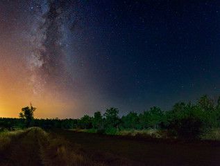 Starry sky with Milky Way galaxy over the summer night rural landscape