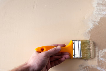 painter's hand painter paints drywall in beige color, copy space