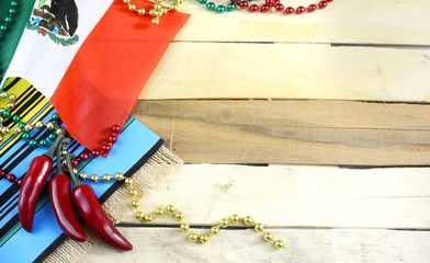 Nice image for Cinco de Mayo, a Mexican celebration, on the 5th of May. Red, green and gold beads with Mexican flag and red chilis on a wooden background. Copy space.