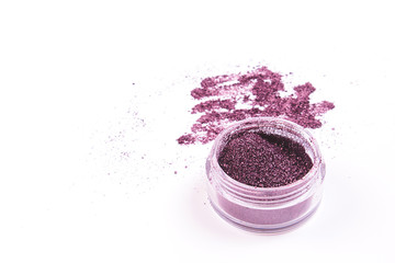 Glass jar with dark glossy eye shadow for make up on white background. Isolated.