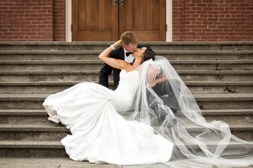 Beautiful bride and groom sensually kissing on church steps